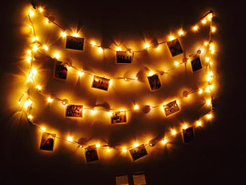 Garland with glowing bulbs and photographs on black background