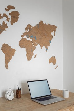 There is a laptop, a mug, an alarm clock and an organizer for stationery on the table, and prints of the continents hang on the white wall.