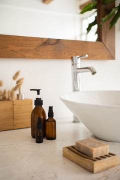 Brown cosmetic bottles are next to the sink