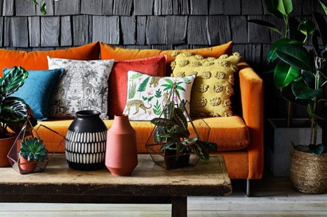 Orange sofa with colorful cushons against a black wall