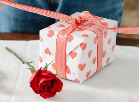 A white gift box with a red gift ribbon and a red rose lie on the table