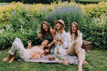 Four girls sit on a bedspread against a background of flowers