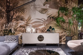 A room with a large wall with a jungle print, a sofa on the left, an armchair on the right, and a chest of drawers with photo frames against the wall