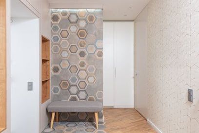 A room with an abstract pattern on one of the walls and a white wardrobe
