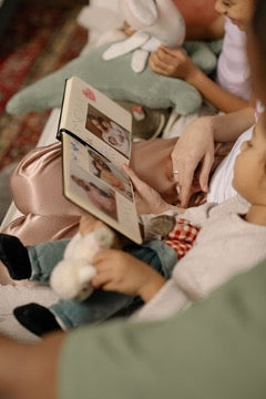 A woman and a child are holding a photo album and watching it