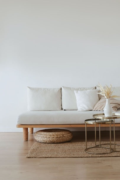 White sofa on a wicker rug against a white wall, next to the sofa a table with a white vase