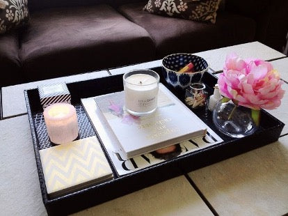 Black tray with candles, book, flower and ashtray