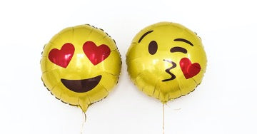 Two yellow balloons, one with a smile and hearts instead of eyes, the second with a kiss smile