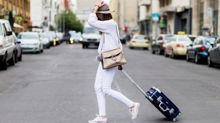Woman in white clothes with a black suitcase crosses the road