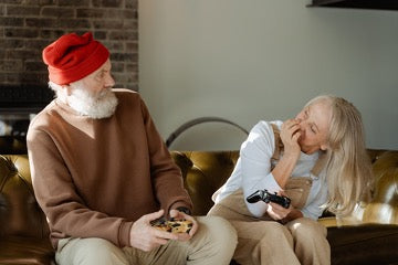 A man in a brown sweater and a red hat sits on a sofa and looks at a woman with long blond hair in a white sweater sitting next to him