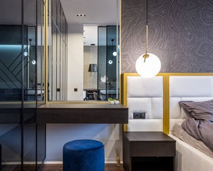 The room has a mirror, bedside table, bed and pendant lamp