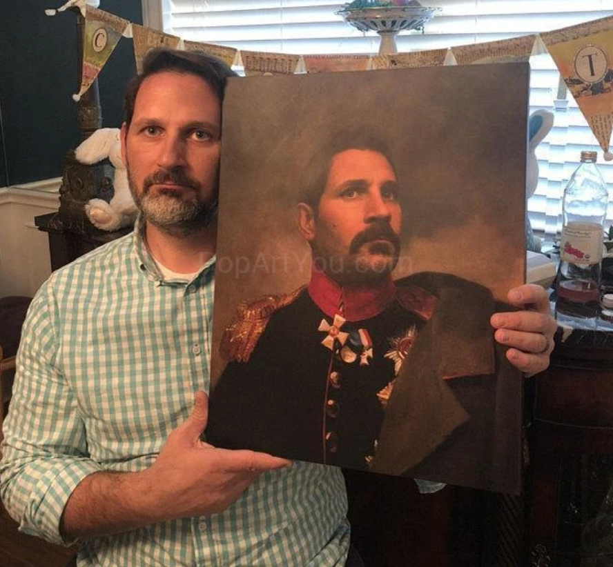 А man holding a portrait of himself dressed in a historical general suit