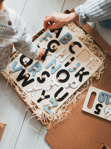 A wooden alphabet puzzle lies on the floor, and the hand of the adult and the hand of the child assemble the puzzle
