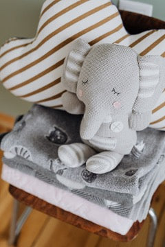 Toy elephant sits on a stack of towels
