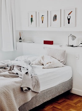A bed with white linens stands against a white wall with a storage niche and four paintings.