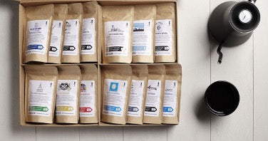 Coffee subscription box next to black coffee pot and cup