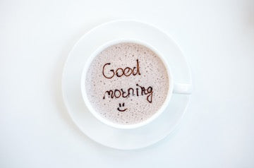 A white cup stands on a white saucer, a drink in the cup with the inscription Good Morning