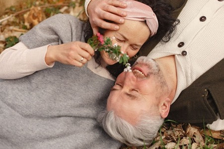 An elderly couple lies on autumn leaves on the ground and smiles, a woman holds a flower near her face, and a man hugs a woman's head
