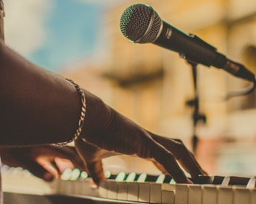 Hands play the piano, above which the microphone is located