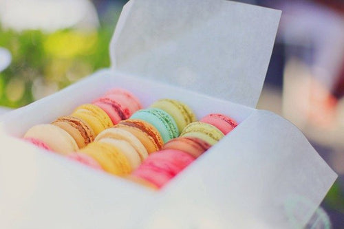 Set of multicolored macaroons in white packaging