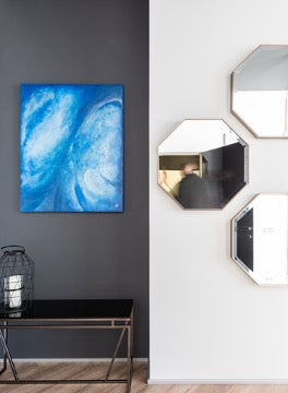 A blue painting hangs on a black wall, three mirrors hang on a white wall