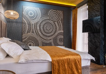 The bed stands against a dark wall with a large painting with abstract circles