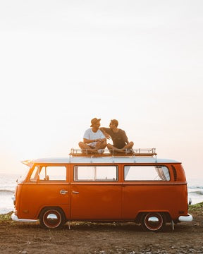 Two men are sitting on the roof of a red mini-bus