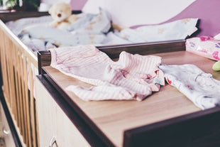 Baby clothes lie on the changing table against the background of a crib