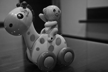 Black and white photo of a toy giraffe on wheels