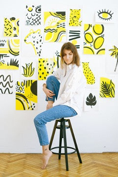 A girl in a white shirt and blue jeans sits on a high chair near a white wall with pictures
