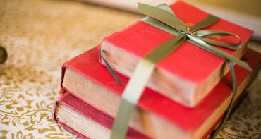 Three books in red covers tied with a golden gift ribbon