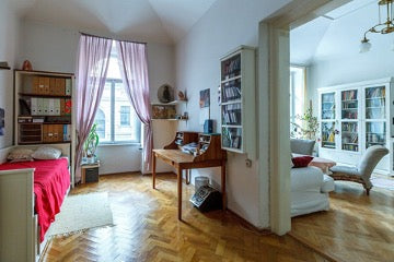 Two rooms are separated by an arch, one with a wall with paintings and an armchair, the other with a window with pink curtains, a bed with a red bedspread, a desk and bookshelves