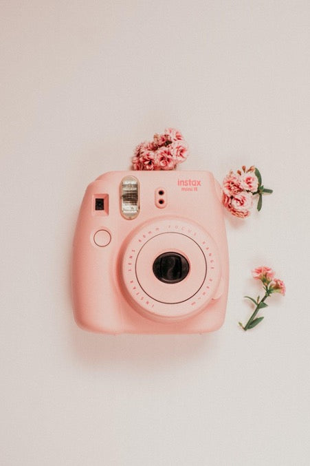 The pink instant camera lies next to small pink flowers