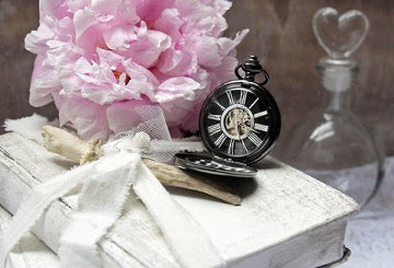 A vintage black clock and a pink flower lie on the white book
