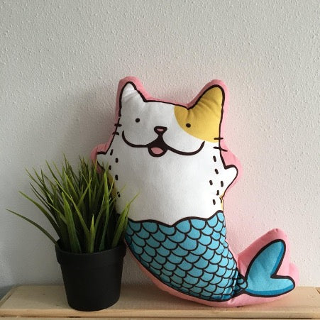 A pillow in the shape of a cat with a fishtail stands against the wall next to a flower in a pot.