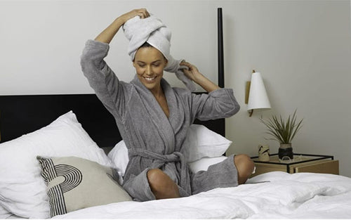 Woman in gray plush robe sits on bed with white linens