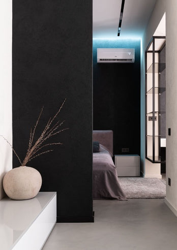 A room with a black partition, from behind which the bed and air conditioning are visible