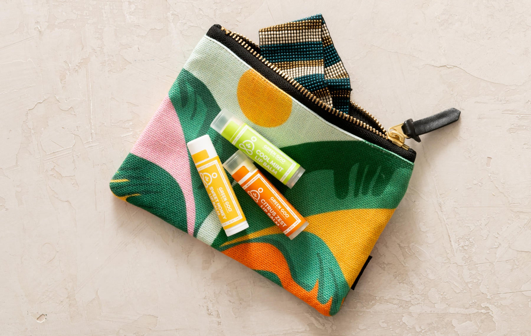 Green Goo's Citrus Zest, Cool Mint, and Sweet Honey lip balms laying on a tropically floral makeup pouch