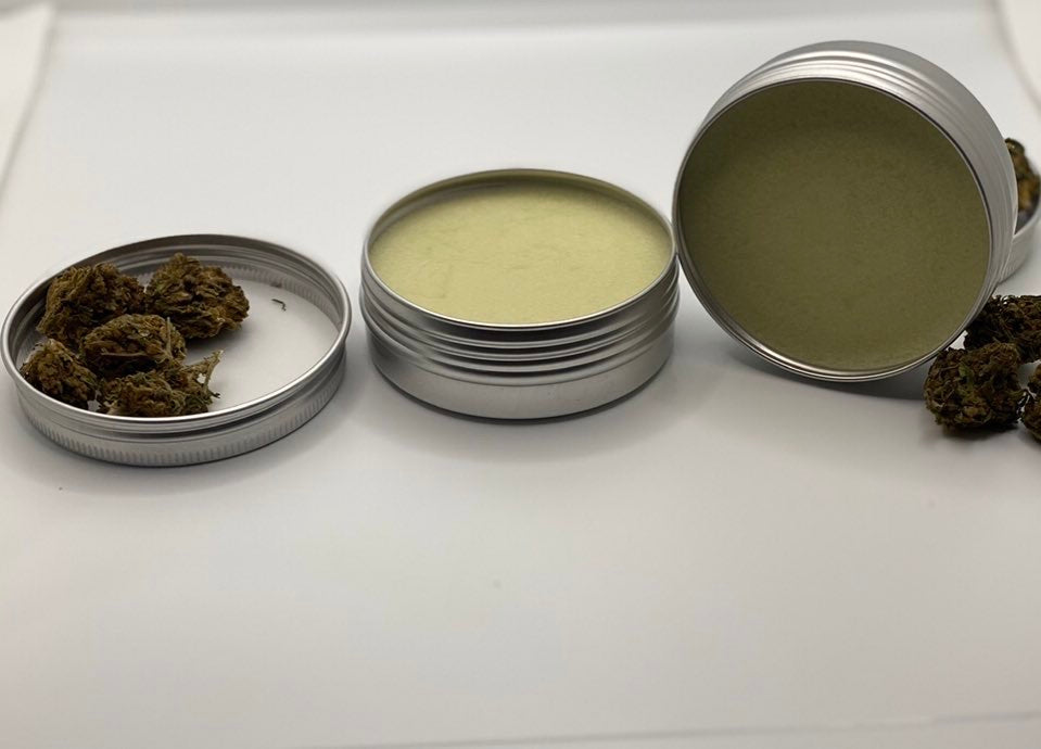 white background. 2 unopened metal jars filled with beige pain cream. lids have weed in them
