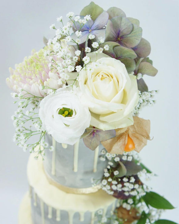 Grey drip cake decorated with fresh flowers - Tuck Box Cakes