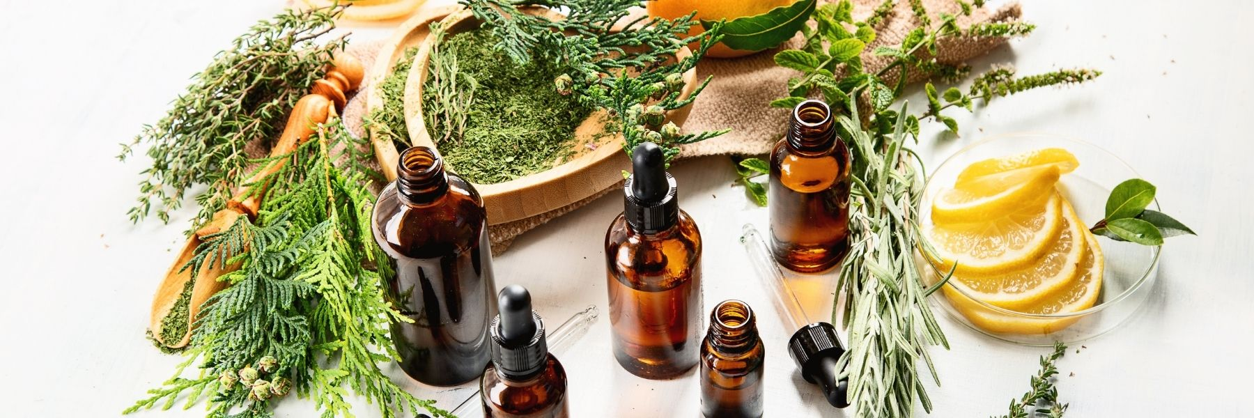 amber glass bottles of essential oils and herbs and lemon with wooden utensils Wild Planet Aromatherapy blog