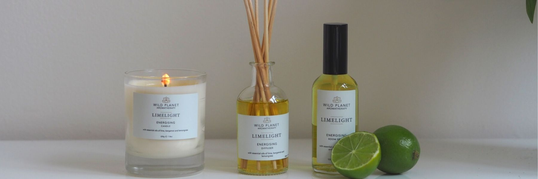 Limelight home fragrance candle, reed diffuser and room spray next to fresh lime sliced in half Wild Planet Aromatherapy blog
