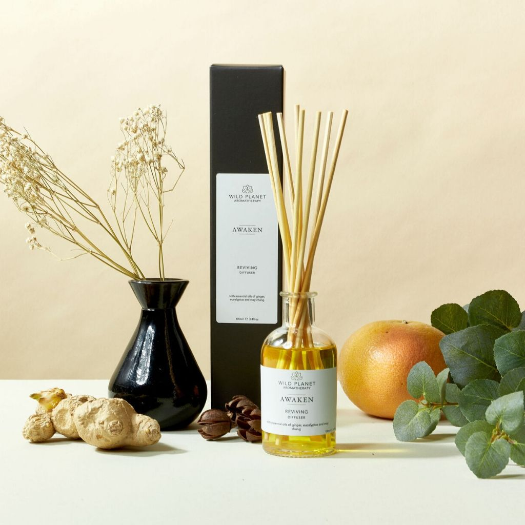 Awaken Reed Diffuser next to grapefruit, eucalyptus and ginger by Wild Planet Aromatherapy