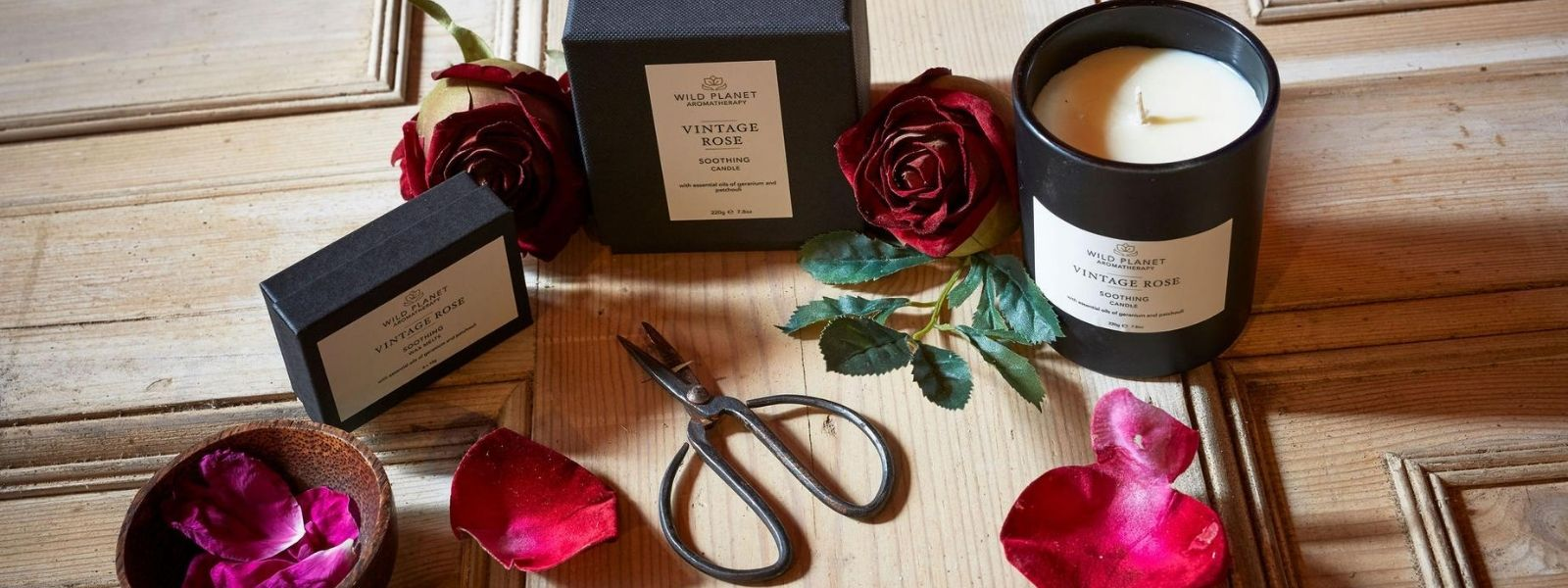 Vintage Rose Candle and box of wax melts on wooden table next to vintage scissors and rose petals in wooden bowl