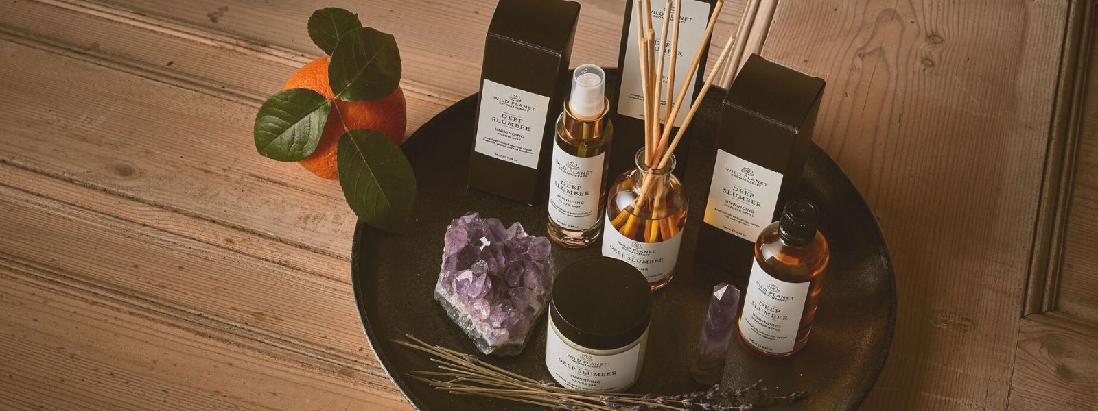Deep Slumber Reed Diffuser, Pillow Mist and Candle Jar by Wild Planet Aromatherapy next to dried lavender, large amethyst crystal and mandarin