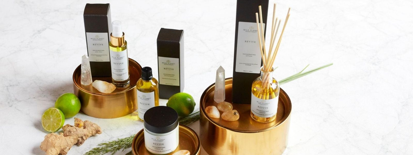 Revive Collection of home fragrances with Citrine crystals showing Reed Diffuser, Candle Jar, Diffuser Refill and room spray next to limes, citrine crystals on gold pedestals on light grey marble background