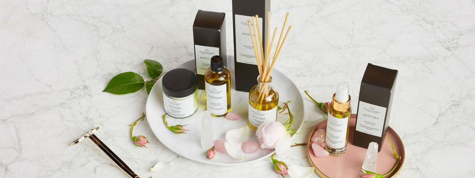 Restore reed diffuser, aura spray and candle jar by Wild Planet Aromatherapy on pink tray with fresh rose buds and rose quartz crystals