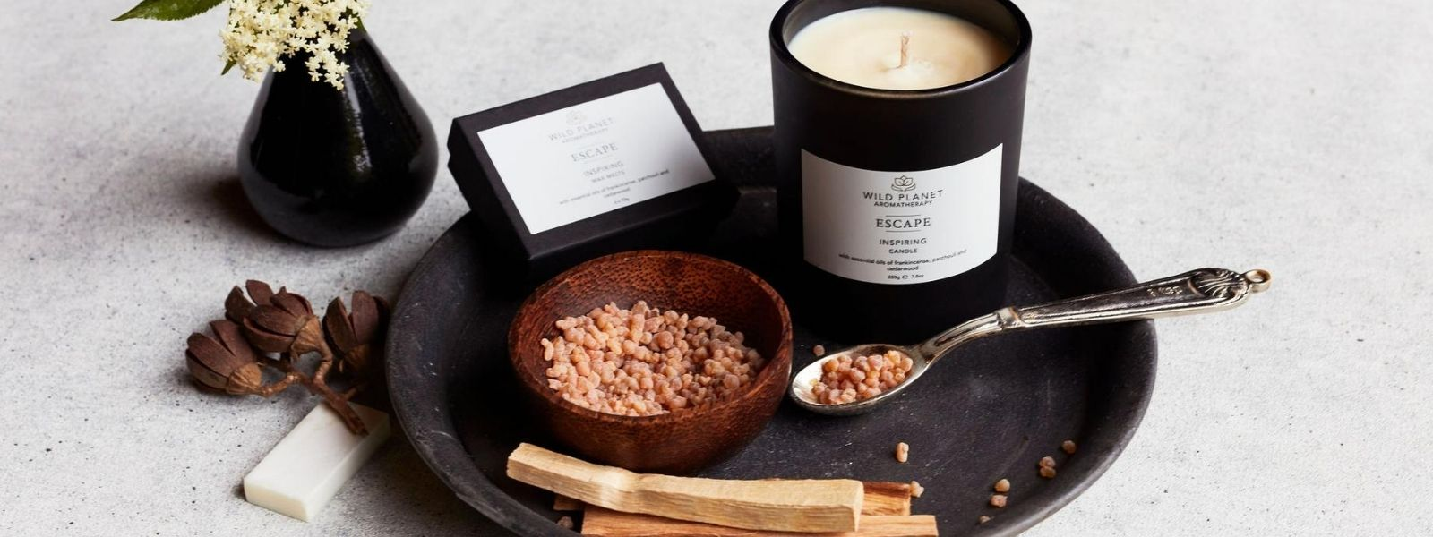 Escape Candle and box of wax melts by Wild Planet Aromatherapy on grey tray next to palo santo sticks and bowl of natural resin
