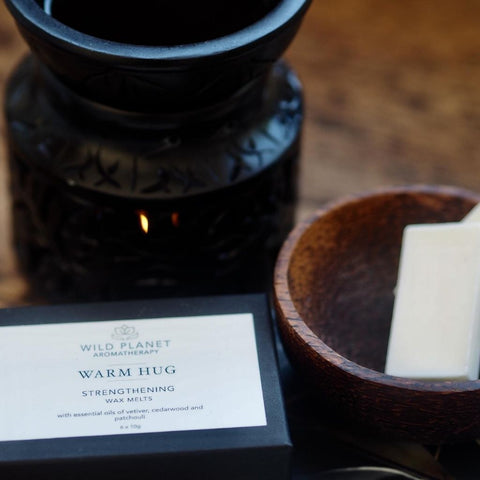 Warm Hug Box of luxury wax melts next to small wooden bowl with two wax melts and black oil burner wax melter by Wild Planet Aromatherapy