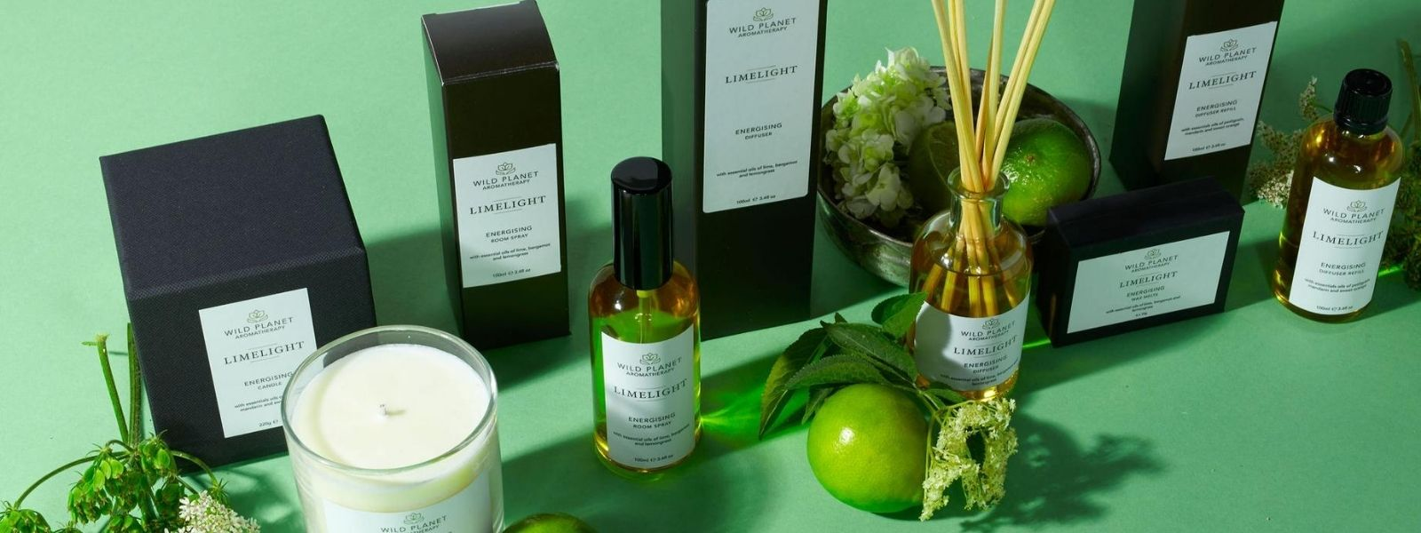 Limelight candle, room spray, reed diffuser and wax melts by Wild Planet Aromatherapy next to fresh limes